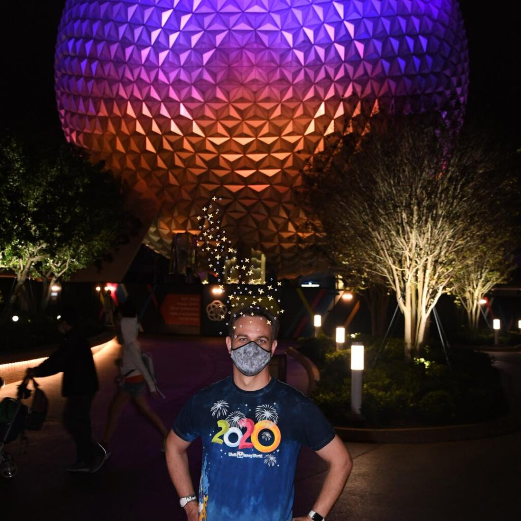 James with hat effect standing in front of Spaceship Earth